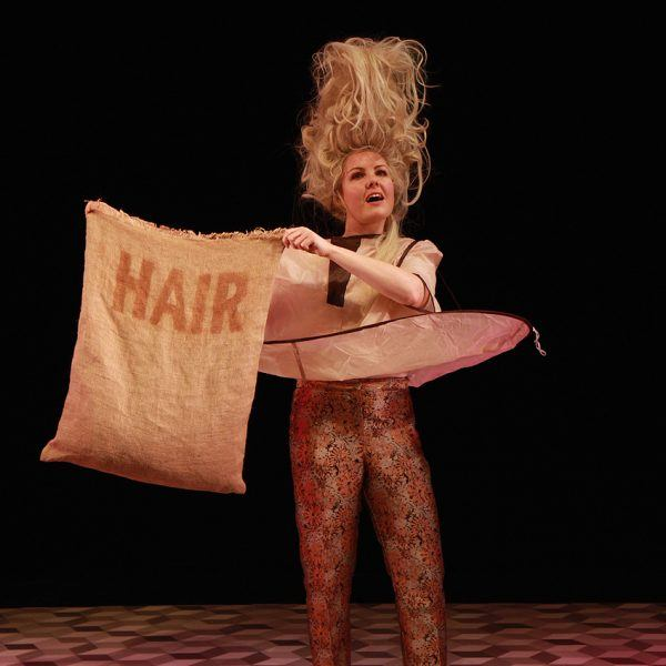 Victoria Melody on stage with a sack of hair in Hair Peace